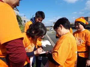 参加者がたすきに名前を書いてリレー
